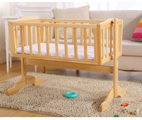 white wooden baby cradle bed with cushion