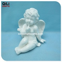 Ceramic sitting angel with one finger on lip Porcelain cherub table decoration